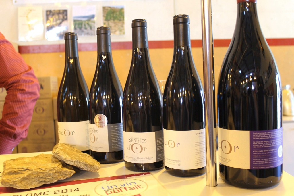 "Les Serines d'Or line-up. The rocks show the make up of the vineyard soils, while the certificate at the bottom was awarded to Encore 2011 by the Un Vin Presque Parfait  (""An Almost Perfect Wine"") Wine Guide 2014."